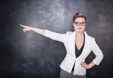Serious woman teacher pointing out. On chalkboard blackboard background Stock Photography