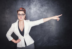 Serious woman teacher pointing out. On chalkboard blackboard background Royalty Free Stock Images