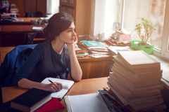 Serious woman thinking in library silence. Serious young woman sitting at a table among books and thinking in library silence Royalty Free Stock Photography