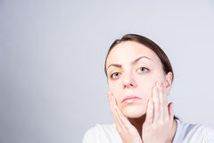 Serious Woman Touching her Face with Two Hands Stock Photography