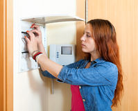 Serious woman turning off the light-switch Stock Photography