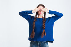 Serious woman with two long braids covered eyes by hands Stock Image