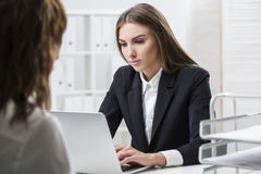 Serious woman is typing. Her colleague is procrastinating Royalty Free Stock Image