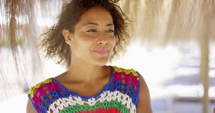 Serious woman under thatch beach umbrella stock video footage