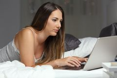 Serious woman using a laptop on the bed in the night royalty free stock photo