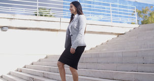 Serious woman walking up staircase Royalty Free Stock Photos