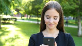 Serious woman walks in a park using phone stock video footage