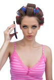 Serious woman wearing hair rollers with phone. Seriuos young woman wearing hair rollers posing with phone on white background Royalty Free Stock Images