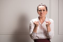 Serious woman wearing white blouse. Half-length portrait of beautiful dark-haired young angry woman wearing white blouse and vinous skirt standing shaking with Stock Image
