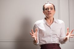 Serious woman wearing white blouse. Half-length portrait of beautiful dark-haired young angry woman wearing white blouse and vinous skirt standing shaking with Stock Photography