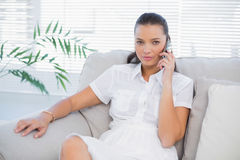 Serious woman in white dress having a phone call Stock Photo