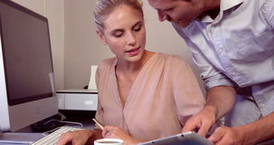 Serious woman working on computer while man showing tablet. In her office at home stock video footage