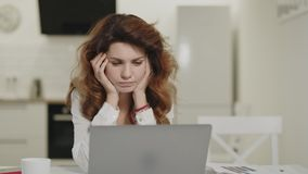Serious woman working computer at remote workplace. Pensive girl look notebook stock footage