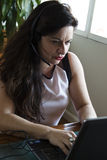 Serious woman working on her laptop at home office Royalty Free Stock Photography