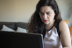 Serious woman working on her laptop at home office Stock Photos