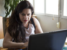 Serious woman working on her laptop at home office Royalty Free Stock Photo
