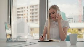 Serious woman working in light office room. Elegant modern business woman with laptop and papers at long table in. Elegant modern businesswoman with laptop and stock video footage