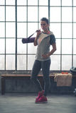 Serious woman in workout gear holding yoga mat in loft gym Royalty Free Stock Photos