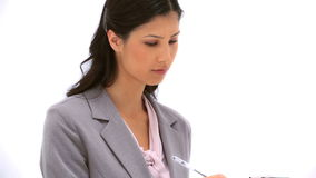 Serious woman writing on a clipboard Stock Photo