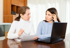 Serious  woman and young daughter at table Royalty Free Stock Photos