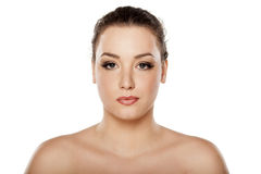 Serious woman. Serious young woman with make up posing on a  white background with naked shoulders Royalty Free Stock Photography