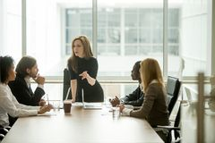 Serious woman boss talking to multiracial team at boardroom meet. Serious women boss scolding employees for bad results or discussing important instructions at Stock Image