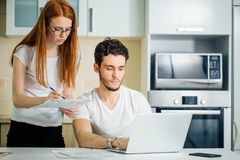 Woman calculate or write accounts with pen, her husband using laptop. Serious women calculate or write accounts with pen, her husband using laptop and checks her Stock Photography