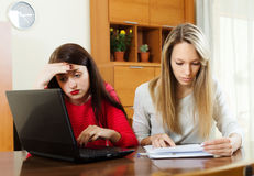Serious women looking  documents with laptop Royalty Free Stock Photography
