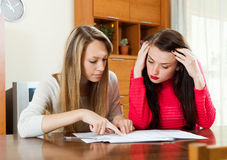 Serious  women looking financial documents at table. In home interior Royalty Free Stock Image