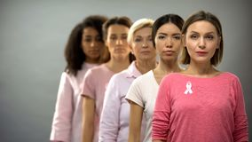 Serious women wearing pink breast cancer awareness ribbons standing in row. Stock photo royalty free stock images