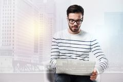 Concentrated smart man looking at the screen of a laptop Stock Image