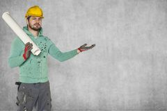 A serious worker with construction plans in his hand. Protective helmet on the head Royalty Free Stock Images