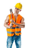 Serious worker. A very muscular and handsome manual worker with a sludgehammer and a yellow helmet isolated over white Royalty Free Stock Images