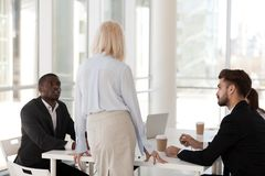 Serious workers sitting at desk listening mature mentor. Rear view of team leader, company owner talking with serious multiracial business people sitting in royalty free stock photos