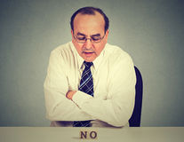 Serious worried business man sitting at table looking at word no Royalty Free Stock Images