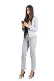 Serious worried business woman typing on her cellphone. Full body length portrait isolated over white studio background Royalty Free Stock Photography