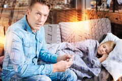 Serious worried man sitting with the thermometer while his ill son sleeping. Worried father. Young serious caring father feeling worried while sitting next to stock image
