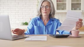Serious worried mature woman reading paper bill to pay online at home.
