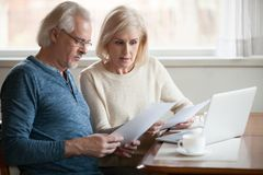 Serious worried senior couple reading documents calculating bill. Serious worried senior couple calculating bills to pay or checking domestic finances stressed royalty free stock images