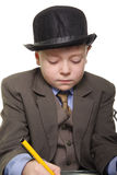 Serious writer. Boy in a suit and hat sitting at desk and writing Stock Photo