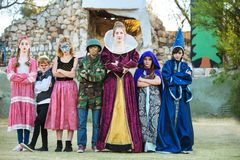 Serious young actors in costume. Seven serious young actors stand with arms folded outside the theater Royalty Free Stock Image