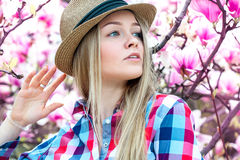 Serious young adult blonde woman with flowers looking away Royalty Free Stock Photo