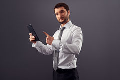 Young adult businessman pointing at the tablet pc Royalty Free Stock Photo
