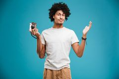 Serious young african curly man. Picture of confused serious young african curly man photographer isolated over blue wall background holding camera Stock Image