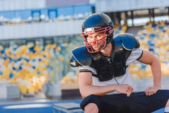 serious young american football player sitting