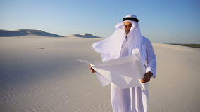Serious young Arabian UAE Sheikh businessman considering construction plan, standing among wide desert on hot summer day. Beautiful Emirate Sheikh businessman stock video footage