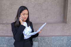 Serious young asian business woman, student talks on phone, hold Royalty Free Stock Image