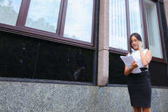 Serious young asian business woman, student talks on phone, hold Royalty Free Stock Images