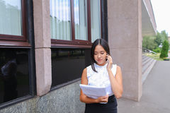 Serious young asian business woman, student talks on phone, hold Stock Photography