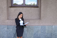 Serious young asian business woman, student talks on phone, hold Stock Photos
